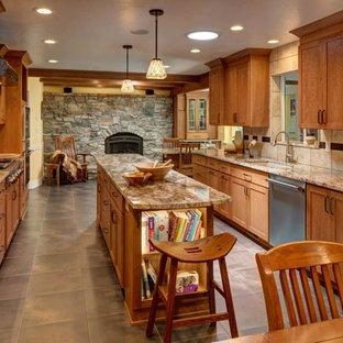 ソルトレイクシティの広いサンタフェスタイルのおしゃれなキッチン (アンダーカウンターシンク、シェーカースタイル扉のキャビネット、淡色木目調キャビネット、御影石カウンター、ベージュキッチンパネル、磁器タイルのキッチンパネル、シルバーの調理設備、磁器タイルの床、グレーの床) の写真