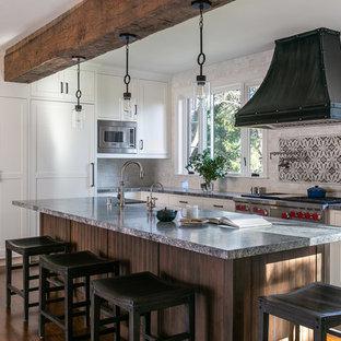 サンフランシスコの大きい地中海スタイルのおしゃれなキッチン (エプロンフロントシンク、シェーカースタイル扉のキャビネット、ヴィンテージ仕上げキャビネット、大理石カウンター、白いキッチンパネル、セラミックタイルのキッチンパネル、パネルと同色の調理設備、濃色無垢フローリング、茶色い床、グレーのキッチンカウンター) の写真