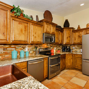 Mid-sized country u-shaped eat-in kitchen in Phoenix with a farmhouse sink, raised-panel cabinets, light wood cabinets, granite benchtops, orange splashback, mosaic tile splashback, stainless steel appliances, porcelain floors and no island.