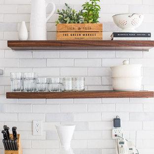 シアトルの中サイズのラスティックスタイルのおしゃれなキッチン (ドロップインシンク、落し込みパネル扉のキャビネット、ベージュのキャビネット、タイルカウンター、白いキッチンパネル、レンガのキッチンパネル、白い調理設備、無垢フローリング、茶色い床、ベージュのキッチンカウンター) の写真