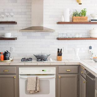 シアトルの中くらいのラスティックスタイルのおしゃれなキッチン (ドロップインシンク、落し込みパネル扉のキャビネット、ベージュのキャビネット、タイルカウンター、白いキッチンパネル、レンガのキッチンパネル、白い調理設備、無垢フローリング、茶色い床、ベージュのキッチンカウンター) の写真