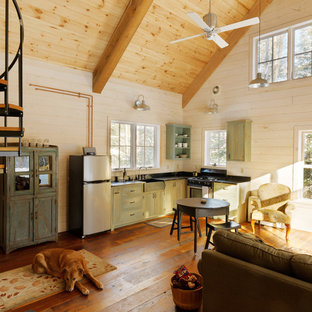 Inspiration for a small country l-shaped open plan kitchen in Burlington with green cabinets, stainless steel appliances, medium hardwood floors, no island, a farmhouse sink, soapstone benchtops, black splashback and flat-panel cabinets.