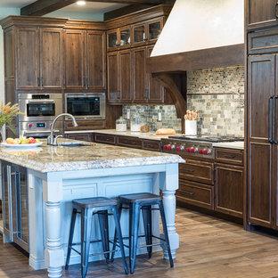 セントルイスの大きいラスティックスタイルのおしゃれなキッチン (ドロップインシンク、フラットパネル扉のキャビネット、中間色木目調キャビネット、木材カウンター、緑のキッチンパネル、大理石のキッチンパネル、パネルと同色の調理設備、無垢フローリング、茶色い床) の写真