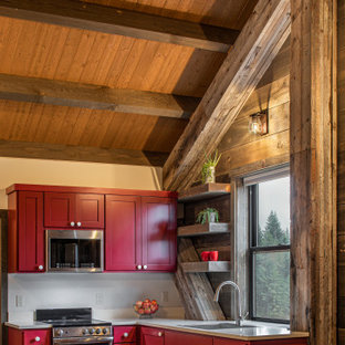 Design ideas for a small rustic l-shaped kitchen/diner in Seattle with a built-in sink, shaker cabinets, red cabinets, engineered stone countertops, white splashback, engineered quartz splashback, stainless steel appliances, medium hardwood flooring, an island and white worktops.