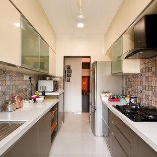 ムンバイのアジアンスタイルのおしゃれなII型キッチン (アンダーカウンターシンク、フラットパネル扉のキャビネット、グレーのキャビネット、マルチカラーのキッチンパネル、シルバーの調理設備の、白い床、白いキッチンカウンター) の写真