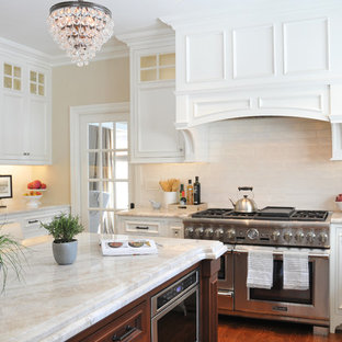 Design ideas for a large transitional u-shaped open plan kitchen in Boston with an undermount sink, recessed-panel cabinets, white cabinets, marble benchtops, white splashback, ceramic splashback, panelled appliances, medium hardwood floors, with island, brown floor and beige benchtop.