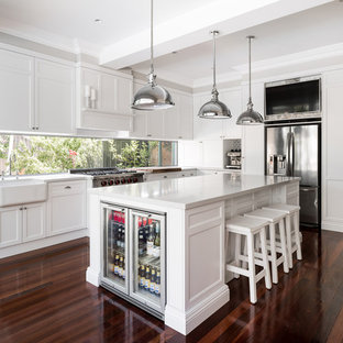 This is an example of a mid-sized transitional l-shaped eat-in kitchen in Perth with shaker cabinets, white cabinets, quartz benchtops, white splashback, window splashback, stainless steel appliances, with island, a farmhouse sink, dark hardwood floors and brown floor.