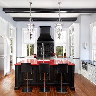 Inspiration för ett avskilt vintage röd rött l-kök, med en rustik diskho, vita skåp, bänkskiva i kvarts, svart stänkskydd, rostfria vitvaror, mellanmörkt trägolv, en köksö och luckor med glaspanel