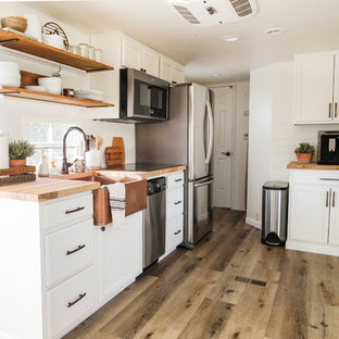 Small farmhouse kitchen designs - Example of a small farmhouse galley laminate floor and gray floor kitchen design in Portland with a farmhouse sink, raised-panel cabinets, white cabinets, wood countertops, white backsplash, porcelain backsplash, stainless steel appliances and no island