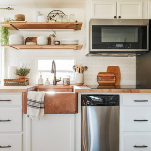 Small farmhouse kitchen designs - Kitchen - small cottage galley laminate floor and gray floor kitchen idea in Portland with a farmhouse sink, raised-panel cabinets, white cabinets, wood countertops, white backsplash, porcelain backsplash, stainless steel appliances and no island