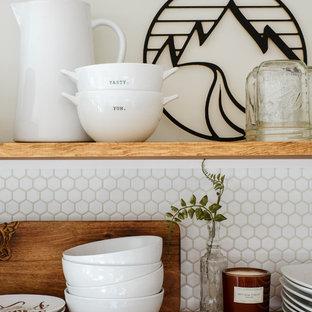 Zweizeilige, Kleine Landhausstil Küche ohne Insel mit Landhausspüle, profilierten Schrankfronten, weißen Schränken, Arbeitsplatte aus Holz, Küchenrückwand in Weiß, Rückwand aus Porzellanfliesen, Küchengeräten aus Edelstahl, Laminat und grauem Boden in Portland