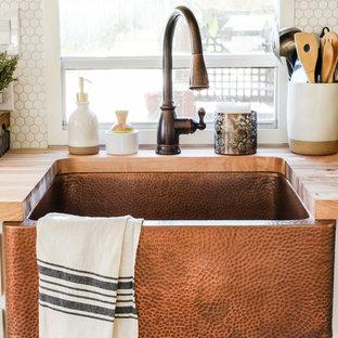 Idéer för små lantliga parallellkök, med en rustik diskho, luckor med upphöjd panel, vita skåp, träbänkskiva, vitt stänkskydd, stänkskydd i porslinskakel, rostfria vitvaror, laminatgolv och grått golv