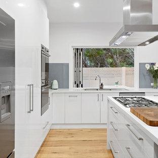 メルボルンのビーチスタイルのおしゃれなキッチン (ドロップインシンク、フラットパネル扉のキャビネット、白いキャビネット、グレーのキッチンパネル、ガラス板のキッチンパネル、シルバーの調理設備の、淡色無垢フローリング、ベージュの床、白いキッチンカウンター) の写真