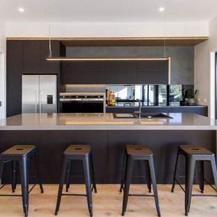 Design ideas for a mid-sized industrial galley kitchen in Melbourne with a drop-in sink, flat-panel cabinets, black cabinets, quartz benchtops, black splashback, mirror splashback, stainless steel appliances, light hardwood floors, beige floor, grey benchtop and a peninsula.