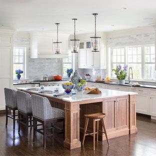 Große, Offene Klassische Küche in L-Form mit Unterbauwaschbecken, Schrankfronten im Shaker-Stil, weißen Schränken, Marmor-Arbeitsplatte, Küchenrückwand in Grau, braunem Holzboden, Kücheninsel, Küchengeräten aus Edelstahl und Rückwand aus Marmor in New York