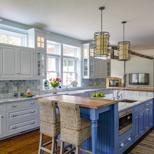 Traditional open concept kitchen inspiration - Example of a classic dark wood floor open concept kitchen design in Boston with an undermount sink, raised-panel cabinets, white cabinets, multicolored backsplash, stainless steel appliances, an island and multicolored countertops