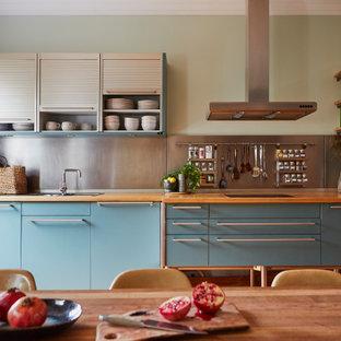 Einzeilige Stilmix Wohnküche ohne Insel mit Einbauwaschbecken, flächenbündigen Schrankfronten, blauen Schränken, Arbeitsplatte aus Holz, Küchenrückwand in Metallic, Rückwand aus Metallfliesen und brauner Arbeitsplatte in London