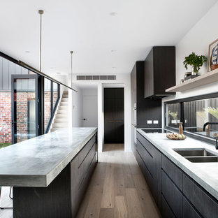 This is an example of a modern galley kitchen in Melbourne with an undermount sink, flat-panel cabinets, dark wood cabinets, concrete benchtops, window splashback, panelled appliances, medium hardwood floors, with island, beige floor and grey benchtop.