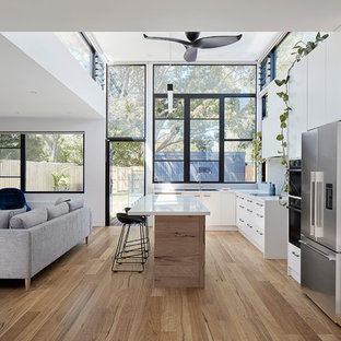 Scandinavian l-shaped open plan kitchen in Melbourne with flat-panel cabinets, white cabinets, stainless steel appliances, medium hardwood floors, with island, brown floor and white benchtop.