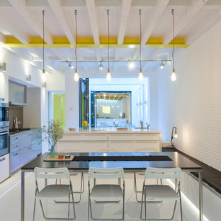 Design ideas for a large modern single-wall kitchen/diner in London with flat-panel cabinets, white cabinets, stainless steel appliances, an island and white floors.