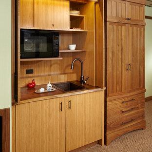 Esempio di una piccola cucina lineare etnica con lavello da incasso, ante lisce, ante in legno chiaro, elettrodomestici neri, moquette e nessuna isola