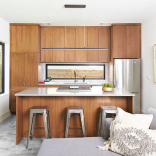Contemporary open concept kitchen designs - Inspiration for a contemporary single-wall gray floor open concept kitchen remodel in Austin with flat-panel cabinets, medium tone wood cabinets, window backsplash, stainless steel appliances, an island and gray countertops