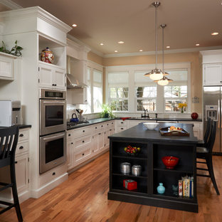 Inspiration for a mid-sized traditional l-shaped eat-in kitchen in Denver with shaker cabinets, white cabinets, soapstone benchtops, white splashback, subway tile splashback, stainless steel appliances, a drop-in sink, light hardwood floors and with island.