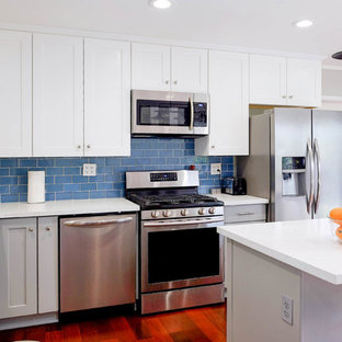 Photo of a small arts and crafts l-shaped eat-in kitchen in Los Angeles with a drop-in sink, shaker cabinets, white cabinets, quartz benchtops, blue splashback, glass tile splashback, stainless steel appliances, medium hardwood floors, with island, brown floor and white benchtop.