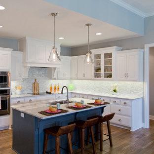 カンザスシティの大きいエクレクティックスタイルのおしゃれなキッチン (アンダーカウンターシンク、ルーバー扉のキャビネット、白いキャビネット、御影石カウンター、マルチカラーのキッチンパネル、ボーダータイルのキッチンパネル、シルバーの調理設備、無垢フローリング、茶色い床) の写真