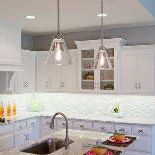 カンザスシティの大きいエクレクティックスタイルのおしゃれなキッチン (アンダーカウンターシンク、ルーバー扉のキャビネット、白いキャビネット、御影石カウンター、マルチカラーのキッチンパネル、ボーダータイルのキッチンパネル、シルバーの調理設備の、無垢フローリング、茶色い床) の写真