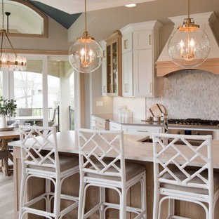 Large french country open concept kitchen ideas - Example of a large french country galley light wood floor and brown floor open concept kitchen design in Kansas City with a farmhouse sink, recessed-panel cabinets, white cabinets, marble countertops, multicolored backsplash, ceramic backsplash, stainless steel appliances, an island and white countertops