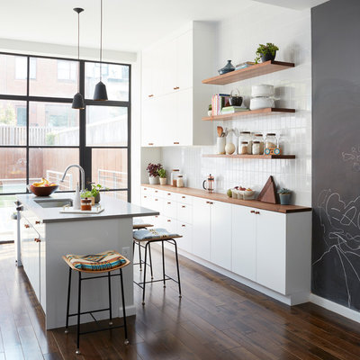 Kitchen - contemporary galley dark wood floor and brown floor kitchen idea in New York with an undermount sink, flat-panel cabinets, white cabinets, wood countertops, white backsplash, an island and brown countertops