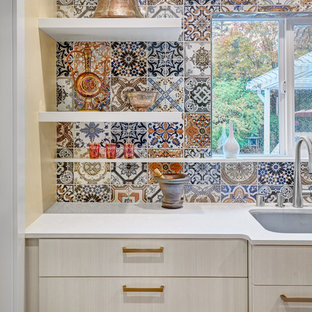 Small mediterranean eat-in kitchen pictures - Inspiration for a small mediterranean u-shaped medium tone wood floor and brown floor eat-in kitchen remodel in Sacramento with an undermount sink, flat-panel cabinets, white cabinets, quartz countertops, multicolored backsplash, porcelain backsplash, paneled appliances and a peninsula