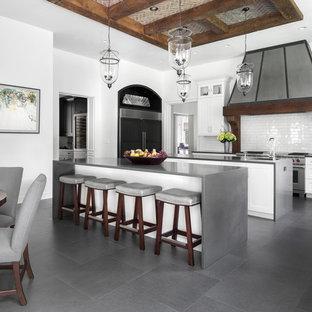 Idéer för mycket stora vintage grått kök, med luckor med infälld panel, vita skåp, vitt stänkskydd, stänkskydd i tunnelbanekakel, rostfria vitvaror, klinkergolv i porslin, flera köksöar och grått golv