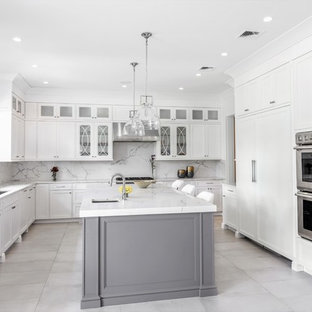 Inspiration for a large transitional u-shaped separate kitchen in New York with an undermount sink, recessed-panel cabinets, white cabinets, marble benchtops, white splashback, marble splashback, stainless steel appliances, marble floors, with island, grey floor and white benchtop.