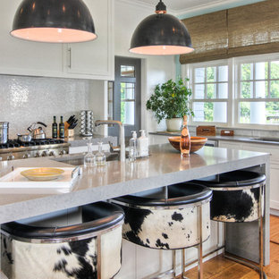 Inspiration for a beach style kitchen remodel in New York with an undermount sink, shaker cabinets, white cabinets, white backsplash, mosaic tile backsplash and stainless steel appliances