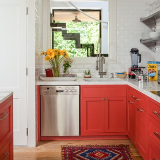 Foto de cocina en L, marinera, pequeña, con fregadero de un seno, armarios estilo shaker, puertas de armario rojas, salpicadero blanco, salpicadero de azulejos tipo metro, electrodomésticos de acero inoxidable, suelo de madera clara y encimeras multicolor