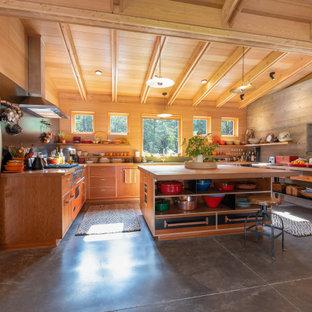 Offene Rustikale Küche in U-Form mit hellbraunen Holzschränken, Arbeitsplatte aus Holz, Küchengeräten aus Edelstahl, Betonboden, Kücheninsel, grauem Boden, flächenbündigen Schrankfronten und brauner Arbeitsplatte in Sonstige