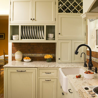 This is an example of a traditional kitchen in Seattle with a farmhouse sink, beaded inset cabinets, green cabinets, granite benchtops, red splashback and terra-cotta splashback.