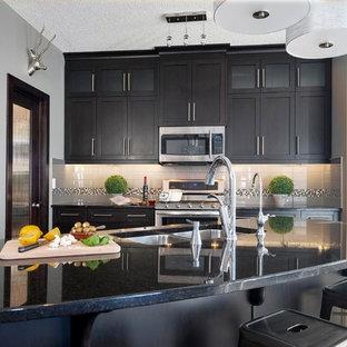 Moderne Küche in L-Form mit Doppelwaschbecken, Glasfronten, dunklen Holzschränken, Granit-Arbeitsplatte, Küchenrückwand in Grau, Rückwand aus Metrofliesen, Küchengeräten aus Edelstahl, dunklem Holzboden und Kücheninsel in Calgary