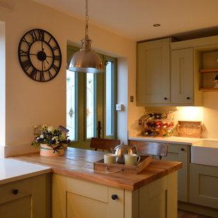 他の地域の小さいシャビーシック調のおしゃれなキッチン (エプロンフロントシンク、シェーカースタイル扉のキャビネット、緑のキャビネット、珪岩カウンター、白いキッチンパネル、石スラブのキッチンパネル、パネルと同色の調理設備、ラミネートの床、茶色い床、白いキッチンカウンター) の写真