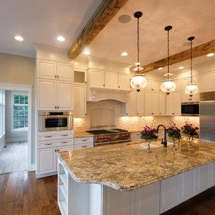 Große Shabby-Chic-Style Wohnküche in L-Form mit weißen Schränken, Granit-Arbeitsplatte, Kücheninsel, Unterbauwaschbecken, Schrankfronten mit vertiefter Füllung, Küchenrückwand in Weiß, Küchengeräten aus Edelstahl, dunklem Holzboden und braunem Boden in Sonstige