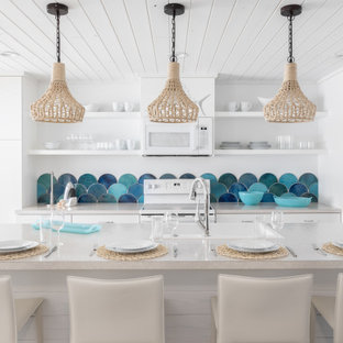Photo of a small beach style galley eat-in kitchen in Tampa with a drop-in sink, flat-panel cabinets, white cabinets, laminate benchtops, blue splashback, mosaic tile splashback, stainless steel appliances, ceramic floors, with island, white floor, white benchtop and wood.