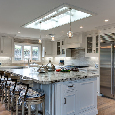 Large transitional l-shaped light wood floor and beige floor eat-in kitchen photo in Orange County with white cabinets, solid surface countertops, gray backsplash, stone tile backsplash, stainless steel appliances, a farmhouse sink, an island and recessed-panel cabinets