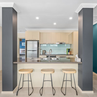 Small beach style galley kitchen in Melbourne with quartz benchtops, with island, a drop-in sink, flat-panel cabinets, beige cabinets, blue splashback, glass sheet splashback, stainless steel appliances, beige floor and brown benchtop.
