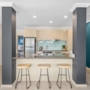 メルボルンの小さいビーチスタイルのおしゃれなキッチン (クオーツストーンカウンター、ドロップインシンク、フラットパネル扉のキャビネット、ベージュのキャビネット、青いキッチンパネル、ガラス板のキッチンパネル、シルバーの調理設備の、ベージュの床、茶色いキッチンカウンター) の写真