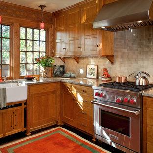 Bild på ett amerikanskt l-kök, med en rustik diskho, luckor med infälld panel, skåp i mellenmörkt trä, granitbänkskiva, stänkskydd i tunnelbanekakel, rostfria vitvaror, en halv köksö, mörkt trägolv och grått stänkskydd