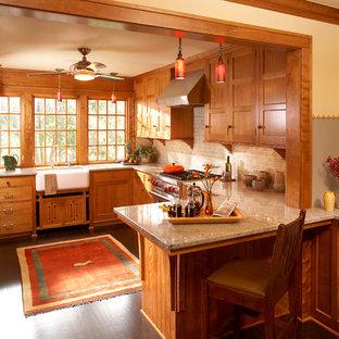 Cette image montre une cuisine américaine craftsman en U avec un évier de ferme, un placard avec porte à panneau encastré, des portes de placard en bois brun, un plan de travail en granite, une crédence en carrelage métro, un électroménager en acier inoxydable, un sol en bois foncé et une péninsule.