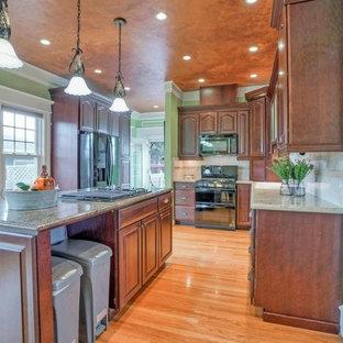 他の地域の中サイズのヴィクトリアン調のおしゃれなキッチン (ドロップインシンク、インセット扉のキャビネット、濃色木目調キャビネット、御影石カウンター、ベージュキッチンパネル、石タイルのキッチンパネル、黒い調理設備) の写真