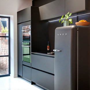 This is an example of a small contemporary galley kitchen in Other with flat-panel cabinets, black cabinets, quartzite benchtops, black splashback, glass sheet splashback, black appliances, painted wood floors, no island, white floor and black benchtop.